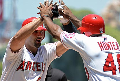 Albert Pujols is greeted by teammate Torii Hunter after connecting for a two-run homer against the Orioles.  (Getty Images)