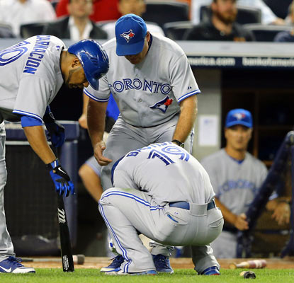 Teammates check on slugger Jose Bautista, who injures his left wrist on a swing in the eighth inning. (Getty Images)