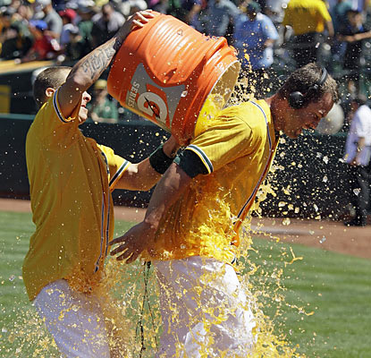 The A's Brandon Hicks (right) receives the hero treatment after he wins the game with a walk-off home run. (AP)
