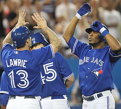 Brett Lawrie leads the greeting party as Edwin Encarnacion arrives after his career-high 27th home run.  (US Presswire)