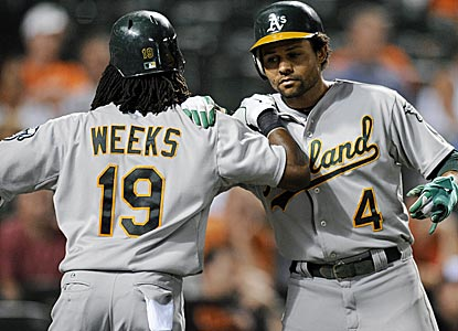 Jemile Weeks and Coco Crisp celebrate after scoring on Seth Smith's double during a six-run ninth inning.  (AP)