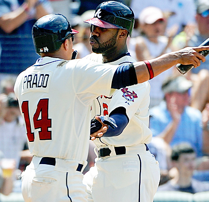 Jason Heyward (right) celebrates with Martin Prado after hitting a solo home run off of Roy Halladay in the first inning. (AP)