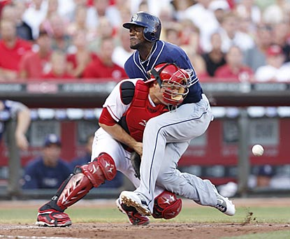 San Diego's Cameron Maybin collides with Cincinnati catcher Devin Mesoraco and scores in the second inning.  (Getty Images)
