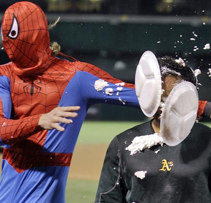 Can you tell the A's are having fun? Josh Reddick, disguised as Spiderman, greets Coco Crisp with shaving cream pies. (AP)