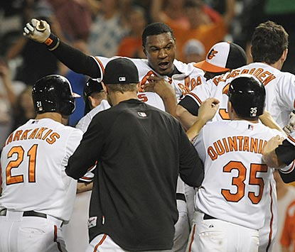 Adam Jones has nowhere to run after driving in the winning run in the 14th inning for his tired but elated teammates.  (AP)