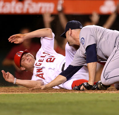 Peter Bourjos slides past Mariners pitcher Josh Kinney in the bottom of the ninth to provide the Angels with the winning run.  (Getty Images)
