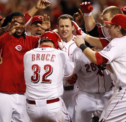 Jay Bruce is mobbed at home plate after winning the game with a three-run blast in the bottom of the ninth.   (US Presswire)