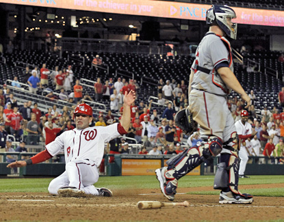 Danny Espinosa scores the winning run on an error in the 13th inning to give the Nationals a 5-4 win. (AP)