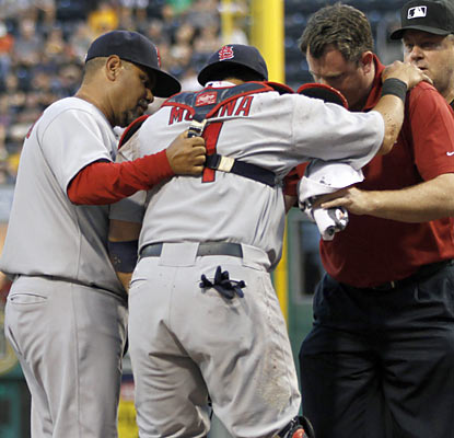 The Cardinals tend to Yadier Molina, who is plastered in a home-plate collision with the Pirates' Josh Harrison. (AP)