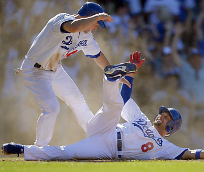 Mark Ellis greets Shane Victorino, who slides safely at home to seal the Dodgers' come-from-behind victory. (AP)