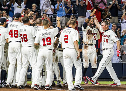 The Braves wait at home plate for Chipper Jones, who delivers a game-ending three-run shot in the ninth. (AP)