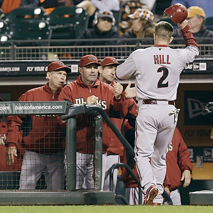 Moments after getting his fifth hit, Aaron Hill comes in to score on Jason Kubel's triple in the 11th inning.  (AP)