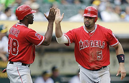 Torii Hunter and Albert Pujols celebrate after scoring on Howie Kendrick's single in the third inning.  (AP)