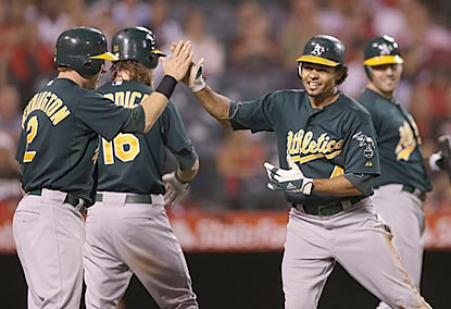Coco Crisp celebrates with Oakland teammates after scoring on an error during the ninth inning.  (Getty Images)