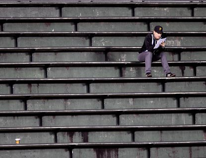 A truly dedicated Pirates fan soldiers on in the Wrigley Field bleachers during the eighth inning.  (AP)
