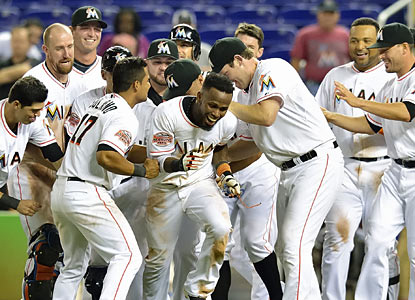 The Marlins swarm Jose Reyes, who provides the winning hit in the 10th inning. (US Presswire)