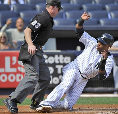 Robinson Cano has to avoid home-plate umpire Lance Barksdale while scoring on a sacrifice fly in the first inning.  (AP)