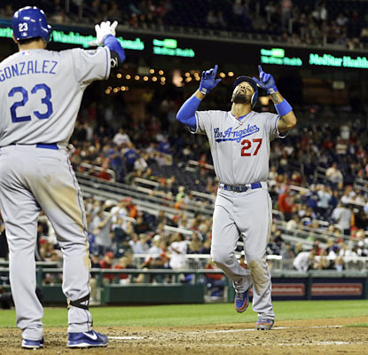 Adrian Gonzalez awaits Matt Kemp, who provides the go-ahead HR in the ninth as well as a phantom run in the fourth. (AP)