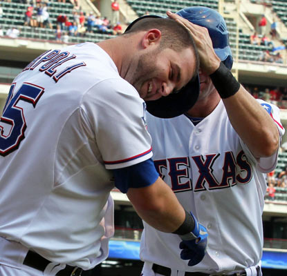 Mike Napoli (left) celebrates his two-run homer with Michael Young as the Rangers keep the A's at bay.  (US Presswire)