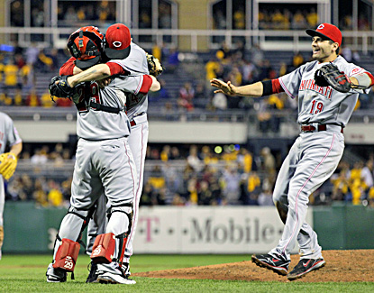 Reds catcher Ryan Hanigan hugs Homer Bailey as first baseman Joey Votto joins moments after the final out against the Pirates. (AP)