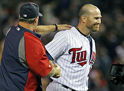 Ryan Doumit is congratulated by batting coach Joe Vavra after the Twins' win. Doumit has a two-run home run and two-run double. (AP)
