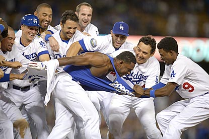 Dodgers teammates rip the uniform top off Elian Herrera in the postgame celebration after his game-ending single.  (AP)