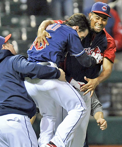 Teammates swarm Jason Donald, who drives in the Indians' winning run with two outs in the 12th. (US Presswire)