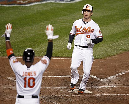 Adam Jones welcomes home Nate McLouth, who scores off a Chris Davis hit in the third inning. (US Presswire)