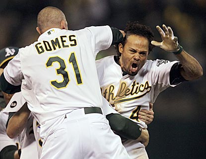 A's outfielder Johnny Gomes is among the first to grab Coco Crisp after his single pushes this AL division series to the limit. (AP)