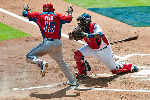 Dominican Republic catcher Carlos Santana tags out Puerto Rico's Irving Falu, preventing a run. (USATSI)