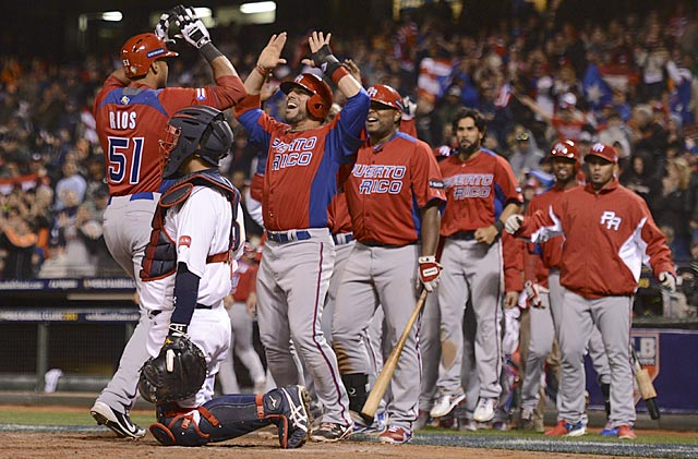 Team Puerto Rico pours out of their dugout to greet Alex Rios after he hits a two-run home run. (USATSI)