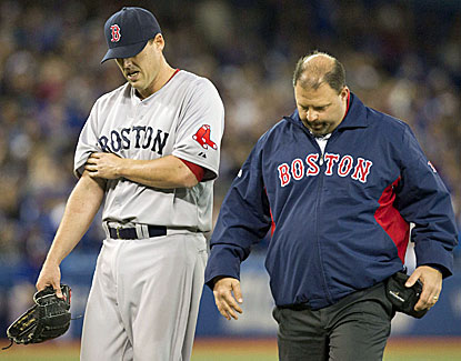 Red Sox starting pitcher John Lackey (left) clutches his right arm as he walks off the field with trainer Rick Jameyson.  (AP)