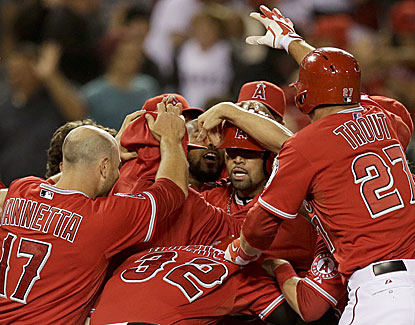 Albert Pujols is mobbed by teammates after hitting a walkoff double to lead the Angels to a 5-4 win over Houston. (AP)