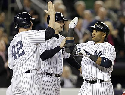 Lyle Overbay (left) and Chris Stewart greet Robinson Cano after they score on Cano's go-ahead home run in the fourth inning.  (AP)