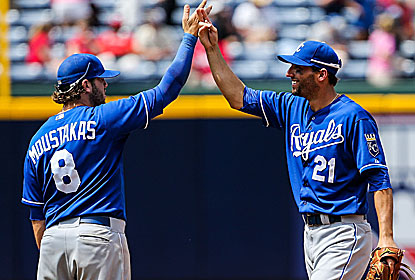 Mike Moustakas and Jeff Francoeur -- who drives in the lone run -- celebrate the win, which denies Atlanta a rare 13-1 start. (USATSI)