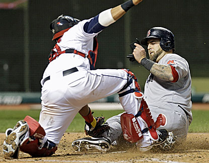 Boston's Mike Napoli beats the tag of Cleveland catcher Carlos Santana in the seventh inning. (AP)