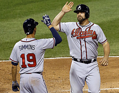 Atlanta's Andrelton Simmons high-fives Evan Gattis after the catcher's go-ahead, pinch-hit homer in the eighth. (AP)