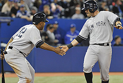 Ex-Blue Jay Vernon Wells (left) gets the rally started in the 11th with a single as the Yankees catch some breaks in the win. (Getty Images)