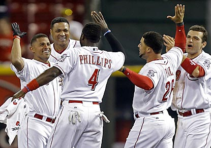 Cincinnati shortstop Cesar Izturis (left) is mobbed by teammates after ending the game with his single in the 13th inning.  (AP)