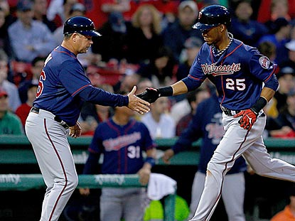 The Twins keep third-base coach Joe Vavra busy in the first two innings, including a home-run handshake with Pedro Florimon.  (Getty Images)