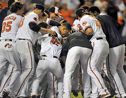 Orioles players mob Nate McLouth after he hit a solo home run in the 10th inning to beat the Yankees. (USATSI)