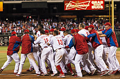 The Phillies mob John Mayberry Jr. after he hit his first career grand slam with two outs in the bottom of the 11th for the win (USATSI)