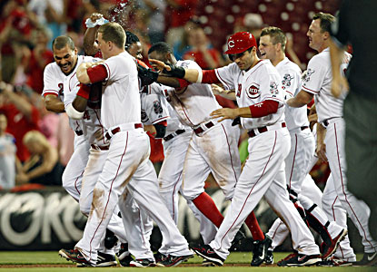 Brandon Phillips is mobbed by teammates after his winning hit during the 13th inning against the Pirates.  (USATSI)