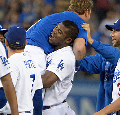 The Dodgers mob A.J. Ellis after his walk-off single to right, scoring Hanley Ramirez just ahead of the tag.  (USATSI)