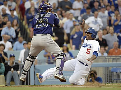 In the second inning, Juan Uribe slides past Wilin Rosario to score the game's first run on Jerry Hairston's double.  (USATSI)