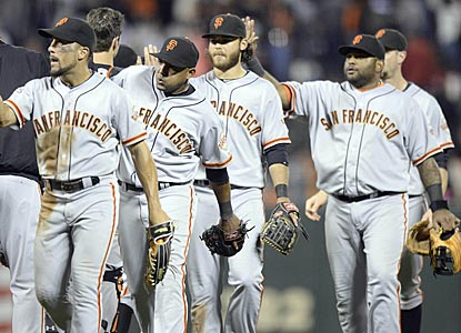 Wearing road uniforms in their home stadium, the Giants celebrate after holding off the Reds in the bottom of the ninth.  (USATSI)