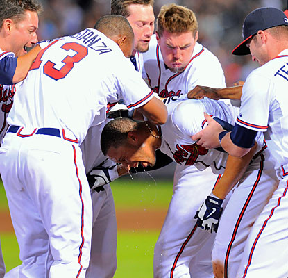 The Braves swarm Andrelton Simmons, who provides the game-winning hit in the 10th to help Atlanta win its fourth straight. (USATSI)