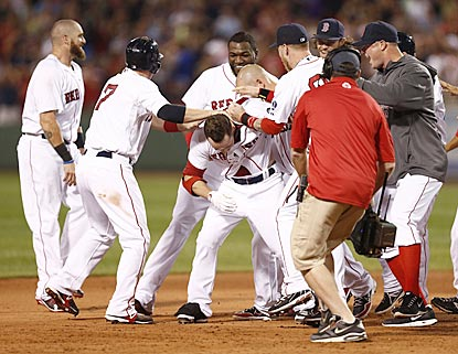 The Red Sox mob Daniel Nava (center) after his single over a drawn-in outfield completes Boston's improbable comeback.  (USATSI)