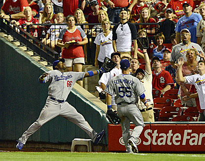 Yasiel Puig's attempt at a leaping catch in the stands is thwarted by a fan. Puig walks 3 times in the game. (USATSI)
