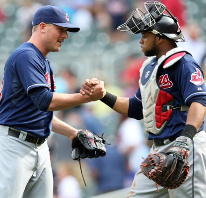 Reliever Joe Smith and catcher Carlos Santana greet after a hard-fought, extra-inning win over the Twins.  (USATSI)
